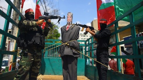 Palestinian terrorists from the Popular Front for the Liberation of Palestine (PFLP) aim their weapons at an effigy depicting US President Donald Trump