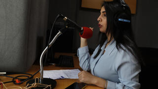 Palestinian journalist Rewaa Mershid works at the studio of ZMN FM radio station in Gaza City