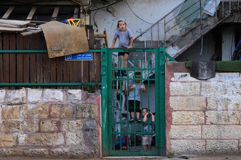 Israeli settler's children look at Palestinians gathering for an Iftar meal, the evening meal with which Muslims end their daily Ramadan fast at sunset, before a demonstration as Palestinian families face eviction, part of an ongoing effort by Jewish Israelis to take control of homes in the Sheikh Jarrah neighbourhood of occupied east Jerusalem