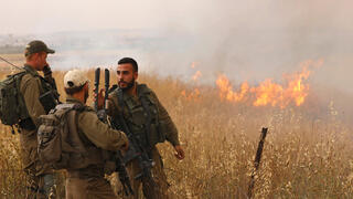 Soldiers near the Gaza border standing in a field burning due to incendiary balloons flown from the Gaza Strip in early May