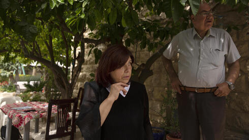 Samira Dajani and her husband, Adel Budeiri, stand in the shade of a tree in the garden of their home, where she has lived since childhood, in the Sheikh Jarrah neighborhood of east Jerusalem