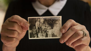 Samira Dajani holds a photo of her family in 1956 after they moved into their home in the Sheikh Jarrah neighborhood of east Jerusalem