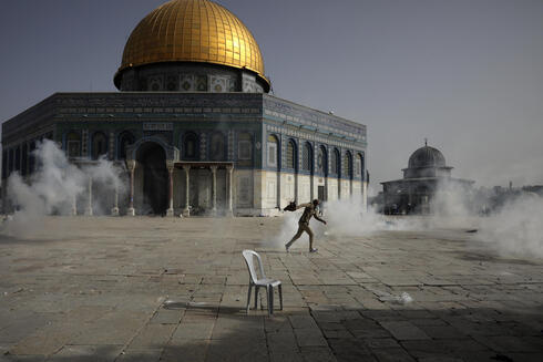 A Palestinian runs away from tear gas during clashes with Israeli security forces in front of the Dome of the Rock Mosque at the al-Aqsa Mosque compound on Monday