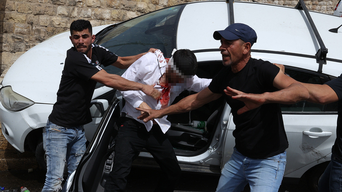 Arab rioters attempting to pull out the driver from the car in Jerusalem