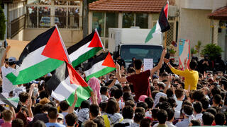 Jordanians hold flags as they demonstrate to express solidarity with the Palestinian people, near the Israeli embassy in Amman, Jordan