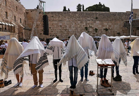 Jewish men pray near the Western Wall in the Old City of Jerusalem as Israel marks Jerusalem Day, May 10, 2021