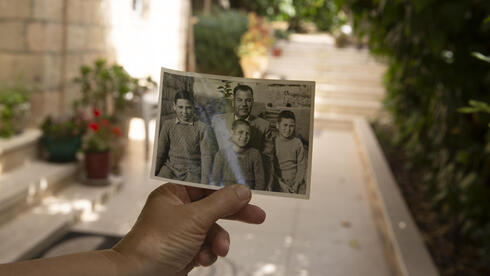 Samira Dajani holds a photo of her father, Fouad Moussa Dajani and his sons, taken in the same place in the courtyard of their home in the Sheikh Jarrah neighborhood