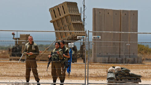IDF soldiers stand next an Iron Dome battery close to the Gaza border
