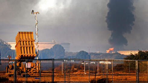 An Iron Dome missile defense battery is seen in the foreground as fire rages at Ashkelon's refinery following a rocket strike from Gaza, May 12, 2021