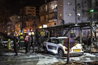Rescue workers at the scene of a Gaza rocket strike in Holon on Tuesday night