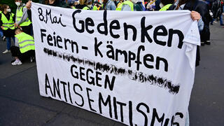 "Demonstrators hold a banner reading ""May 8th, commemoration, celebrate, fight against antisemitism"" during a protest in Berlin"