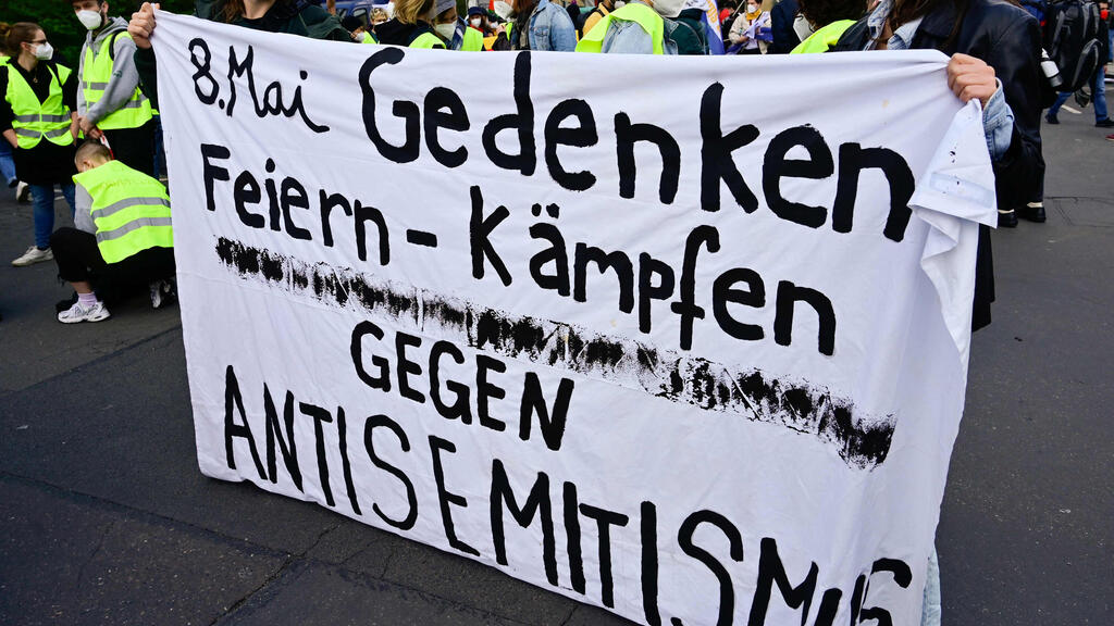 """Demonstrators hold a banner reading """"May 8th, commemoration, celebrate, fight against antisemitism"""" during a protest in Berlin"""