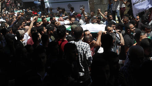 amas mourners carry the bodies of thirteen Hamas militants during their funeral outside of the main mosque in Gaza