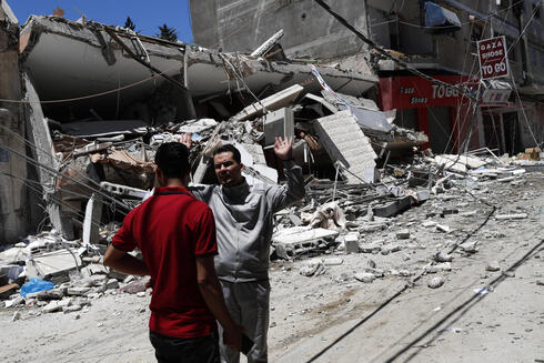 Palestinians react in front of the remains of destroyed building after being hit by Israeli airstrikes in Gaza