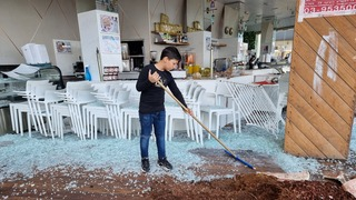 Boy cleans up glass after it was smashed by rioters in Bat Yam