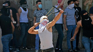 Palestinian rioter uses slingshot to hurl stones at troops in Hebron on Friday