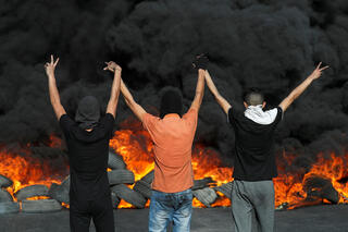 Palestinian protesters burn tires during protests in the West Bank over the Gaza conflict and tensions at the al-Aqsa Mosque, May 16, 2021