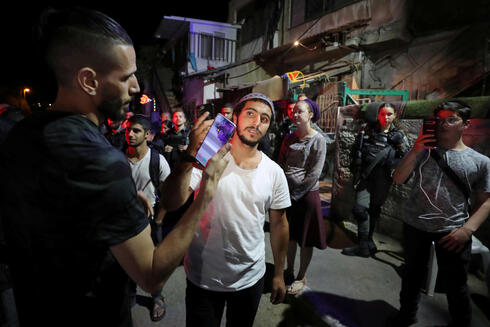 A Jewish resident and a Palestinian protester hold their mobiles to take pictures of each other amid ongoing tension in Sheikh Jarrah, May 5, 2021