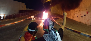 Dozens of masked individuals riot in the Arab city of Umm al-Fahm and set fire to tires on a road leading to a police station