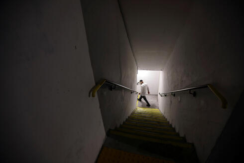 An Israeli man walks down the stairs into a bomb shelter as Israeli-Palestinian cross-border violence continues, in Ashkelon, southern Israel