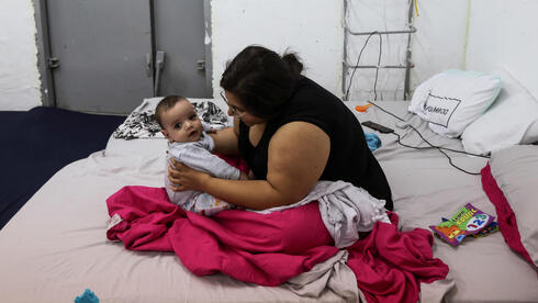 Tsvia Ganon, 28, five-month-old boy, Ori, sit inside a bomb shelter as Israeli-Palestinian cross-border violence continues, in Ashkelon, southern Israel