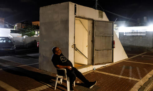 An Israeli man sits by the entrance to a bomb shelter as Israeli-Palestinian cross-border violence continues, in Ashkelon, southern Israel