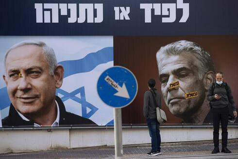 people stand in front of an election campaign billboard for the Likud party showing a portrait of its leader Prime Minister Benjamin Netanyahu, left, and opposition party leader Yair Lapid, in Ramat Gan, Israel