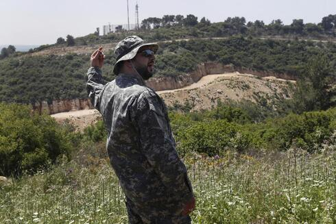 a Hezbollah officer, who identified himself as Ehab, stands in front an Israeli army position, background, as he explains to journalists about the defensive measures established by the Israeli forces, how they cut through the mountain to prevent against any Hezbollah infiltration into Israel, at the Lebanese-Israeli border near the village of Labbouneh, south Lebanon