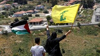 Lebanese wave Hezbollah and Palestinian flags, as they stand in front of the Israeli town of Metula, background, on the Lebanese side of the Lebanese-Israeli border in the southern village of Kfar Kila