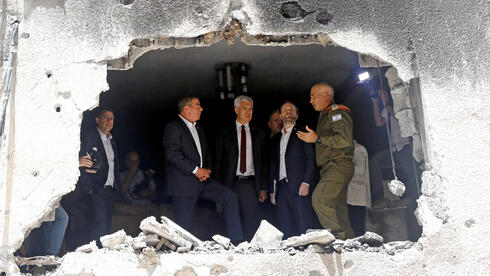 Foreign Minister Gabi Ashkenazi speaks to his Czech counterpart Jakub Kulhanek and Slovak counterpart Ivan Korcok as they visit the site of a building damaged by a rocket launched from the Gaza Strip last week, in Petah Tikva, Israel May 20,