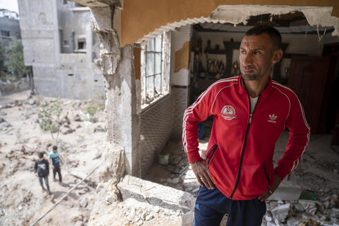 Nader al-Masri, a long-distance runner who participated in dozens of international competitions, including the 2008 Olympics, stands inside his severely damaged home