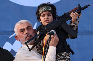 Hamas leader in Gaza Yahya Sinwar holding up a child donning militant garb and holding a firearm during a memorial for victims of latest round of fighting with Israel