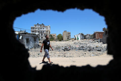 Palestinian man is seen through a damaged stable in the northern Gaza Strip May 24, 2021
