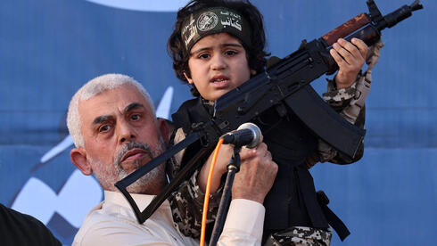 Hamas leader Yahya Sinwar holds the child of an Al-Qassam Brigades fighter, who was killed in the recent fighting with Israel