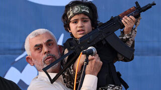 Hamas leader Yahya Sinwar holds the child of an Al-Qassam Brigades fighter, who was killed during the May conflict with Israel