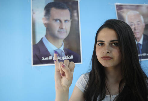 Syrian voter indicates at photo of Syrian President Assad at Damascus polling station on Wednesday