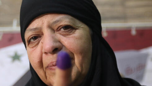 Syrian woman shows her finger marked with ink at after casting her vote in presidential election in Damascus on Wednesday