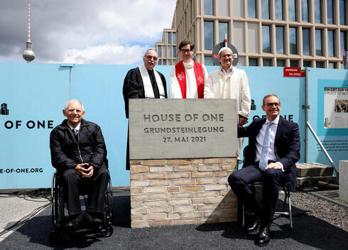 (L-R) President of the German parliament Bundestag, Wolfgang Schaeuble, Rabbi Andreas Nachama, Pastor Gregor Hohberg, Imam Kadir Sanci and Berlin Governing Mayor Michael Mueller pose for a group photo during the laying of the foundation stone ceremony for the multi-religious 'House of One' building in Berlin
