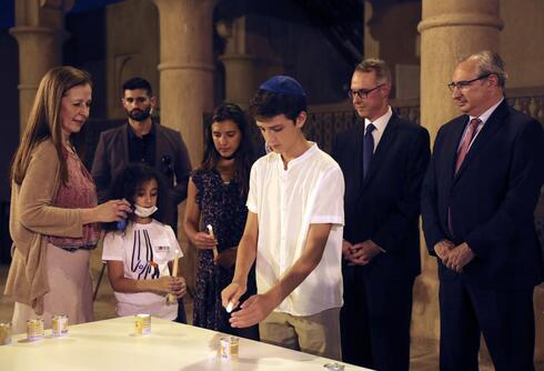 Israeli's Ambassador to the United Arab Emirates, Eitan Na'eh, right, and German Ambassador in UAE, Peter Fischer, second right, watch a candlelight ceremony at an exhibition commemorating the Jewish Holocaust in Dubai