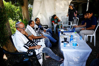 Friends and family members of Yigal Yehoshua, who died after succumbing to his wounds sustained in an attack by Arab lynchers in the mixed city of Lod, wear Jewish prayer shawls during the mourning period following Yehoshua's death, in Moshav Hadid, Israel May 23, 2021