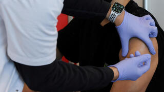 A teenager receives a vaccination against the coronavirus in Tel Aviv, Israel