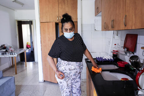 Randa Aweis, who received a kidney donation from Yigal Yehoshua, who died after succumbing to his wounds sustained in an attack by Arab lynchers in the mixed city of Lod, looks on while standing in her kitchen at her home in Jerusalem May 26, 2021