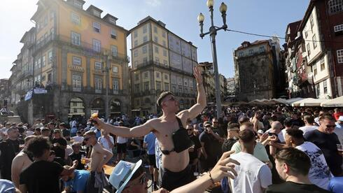 Manchester City supporters drink and chant by the Douro river bank in Porto, Portugal