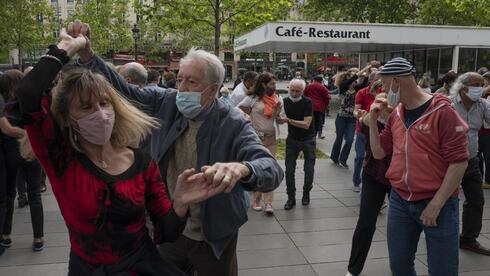 a couple with protective masks on dance at Republic square in Paris