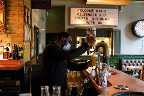a bartender pours a pint of beer at the Prince of Peckham pub, as it reopens to indoor customers, in London