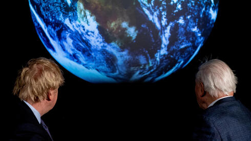 British Prime Minister Boris Johnson and David Attenborough look at a projection of planet Earth