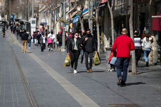 People carry shopping bags as Israel reopens swathes of its economy, while it continues to lift restrictions of a national lockdown to fight the coronavirus disease (COVID-19), in Jerusalem