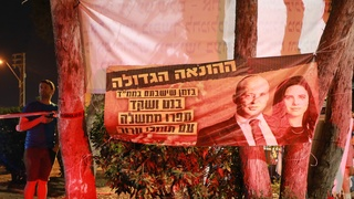 Protesters outside the home of Yamina No. 2 Ayelet Shaked hold a banner accusing her and party leader Naftali Bennett of uniting with supporters of terrorism