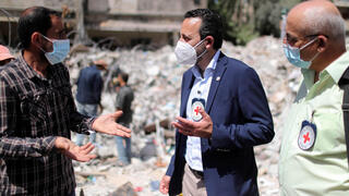 Robert Mardini gestures as he speaks with a Palestinian man near the rubble of a house destroyed in Israeli air strikes during Israeli-Palestinian fighting, in Gaza City