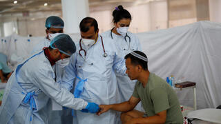 """Health workers tend to an Indian Jew, member of the Bnei Menashe, or the Children of Menashe, one of the """"lost tribes of Israel"""" from the India's northeastern state of Manipur, suffering from the coronavirus disease (COVID-19), at a COVID-19 care facility, inside a Gurudwara or a Sikh Temple, in New Delhi, India"""
